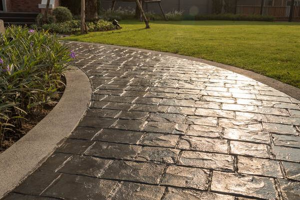 Dark Grey Stamped Concrete Walkway with Light Grey Accents in Backyard